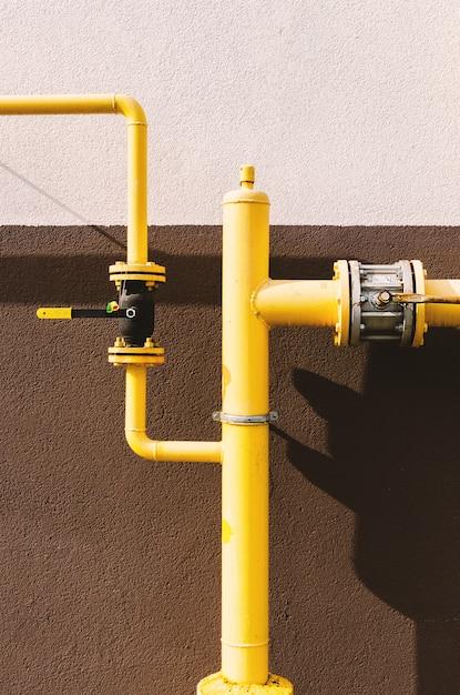 Желтая газовая труба с краном идет вдоль фасада нового многоэтажного дома. Premium Фотографии