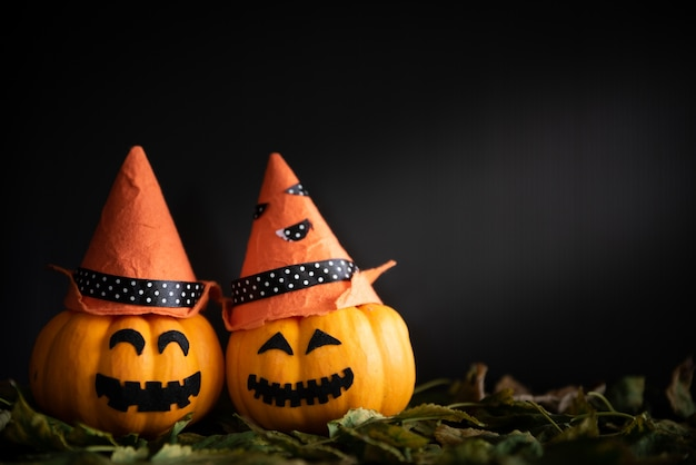 Yellow ghost pumpkins with witch hat in dark room. Premium Photo