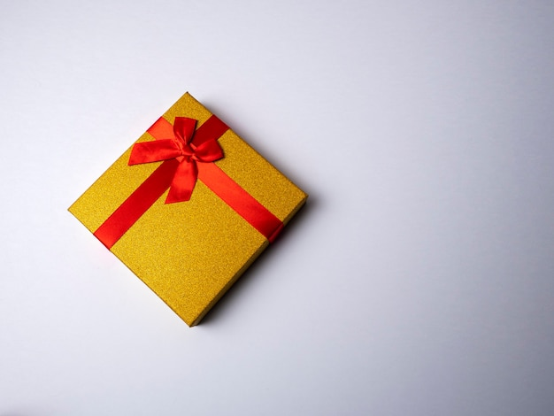 Yellow gift with a red ribbon in the form of a butterfly knot lies on a bright white background Premium Photo
