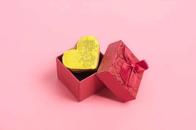 Yellow  gingerbread heart in red box on pink background Premium Photo