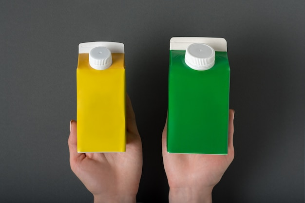 Yellow and green carton box or packaging of tetra pack in a female hands. Premium Photo