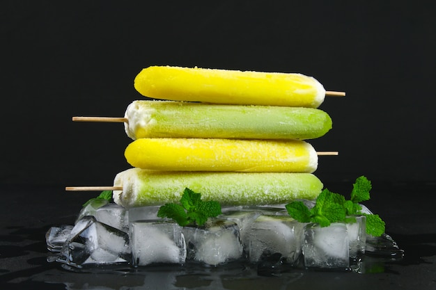 Yellow and green fruit ice cream on a stick with mint on ice on a black table. Premium Photo