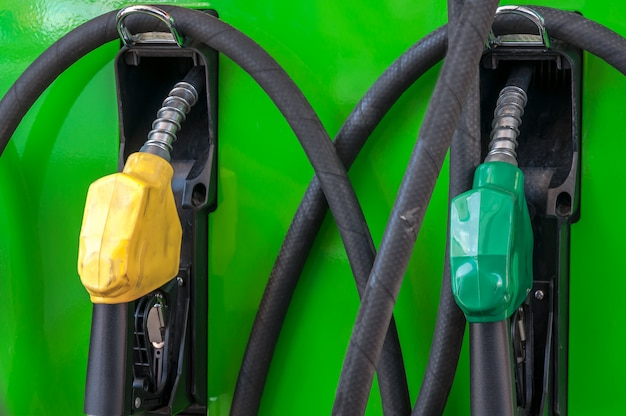 Yellow and green petrol gas pump nozzles in a service station,vfuel nozzle in oil station thailand Premium Photo