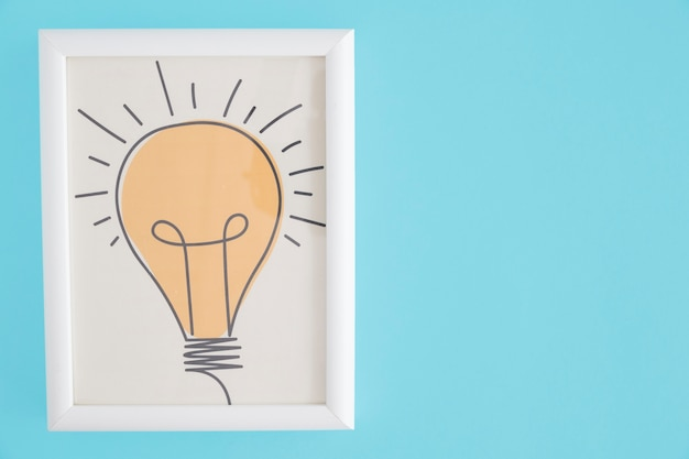 Yellow hand drawn light bulb white frame over blue background Free Photo