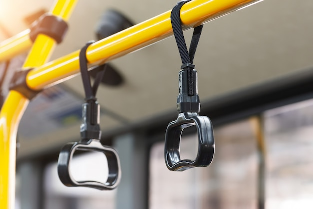 Yellow handrails and black handles to hold passengers steady while the bus is moving. Premium Photo