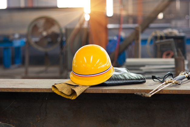 Yellow hardhat and old leather gloves Premium Photo