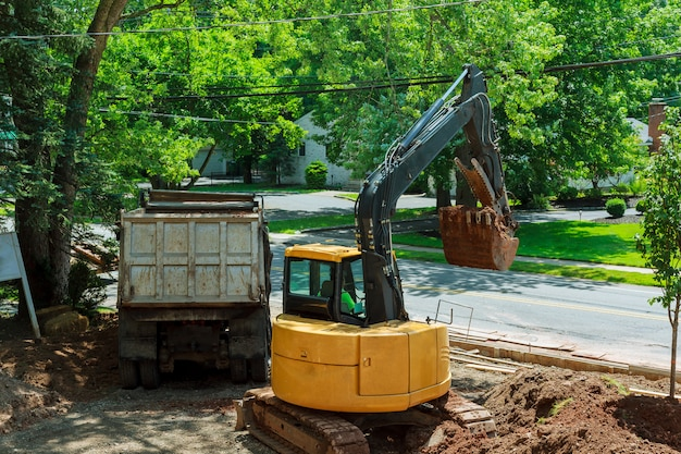 Yellow heavy duty digger working in excavation pit Premium Photo
