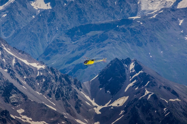 A yellow helicopter on a background of mountains Premium Photo