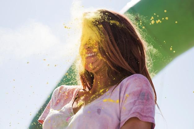 Порошок желтого цвета холи взрывается на лице женщины Бесплатные Фотографии