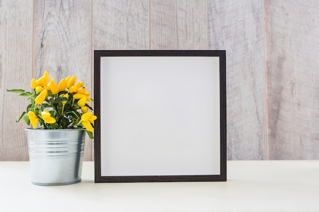 Yellow hot chili peppers in silver pot and white picture frame on table Free Photo