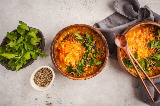Yellow indian vegan lentil soup curry with parsley and sesame in a wooden bowl. Premium Photo