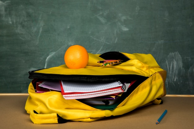 Yellow knapsack with copybooks and orange Free Photo