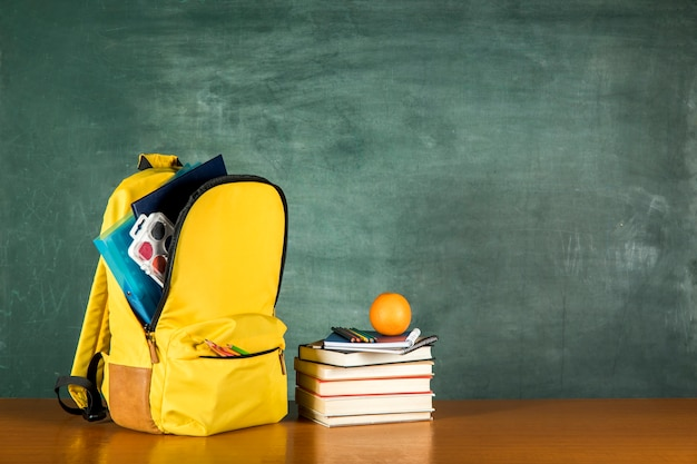 Yellow knapsack with stationery and stacked books Free Photo