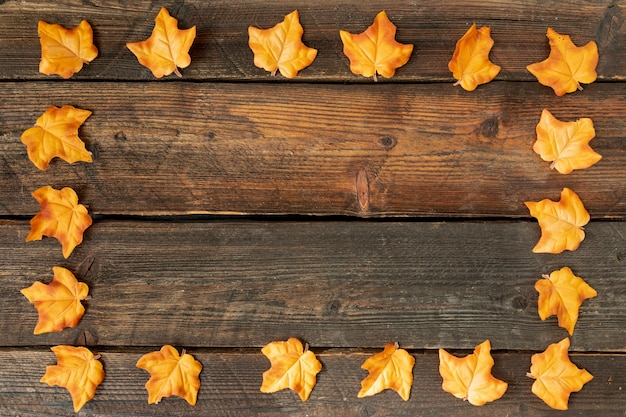 Yellow leaves frame on wooden background with copy space Free Photo