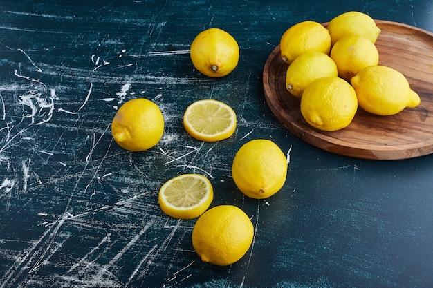 Желтый лимон и дольки на синем фоне в деревянном блюде. Бесплатные Фотографии