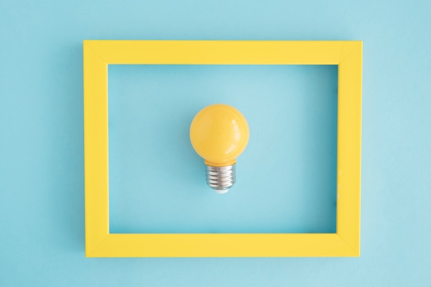 Yellow light bulb frame on blue backdrop Free Photo
