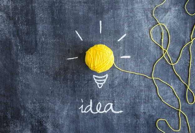 Yellow light bulb made with ball of yarn with idea text on chalkboard Free Photo