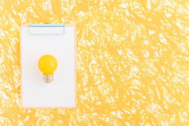 Желтая лампочка на белой бумаге через буфер обмена на желтом фоне Бесплатные Фотографии