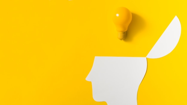 Yellow light bulb over the open paper cut out head against colored background Free Photo