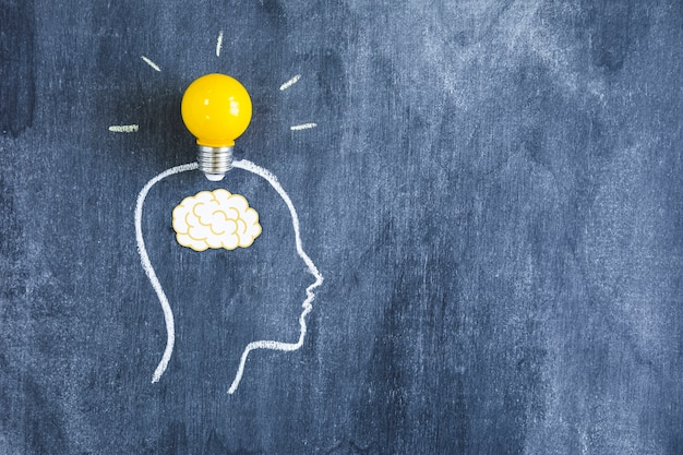 Yellow light bulb over the paper cutout brain on the outline face made with chalk over the blackboard Free Photo