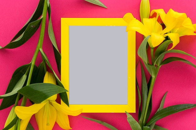 Yellow lily flowers and blank picture frame over the pink; background Free Photo