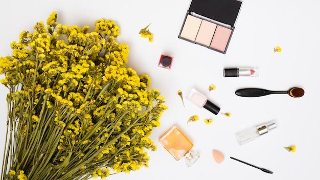 Yellow limonium flower bouquet; nail polish bottle; perfume bottles; lipstick and makeup brush and compact face powder on white background Free Photo