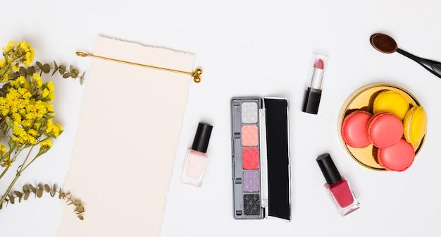 Yellow limonium flower; golden hairpin; white paper; lipstick; nail polish bottles; makeup brush and macaroons on white background Free Photo