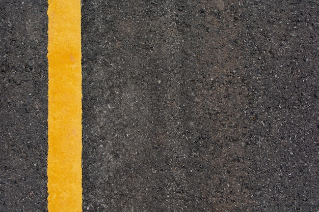 Yellow line on black asphalt road background with copy space Premium Photo