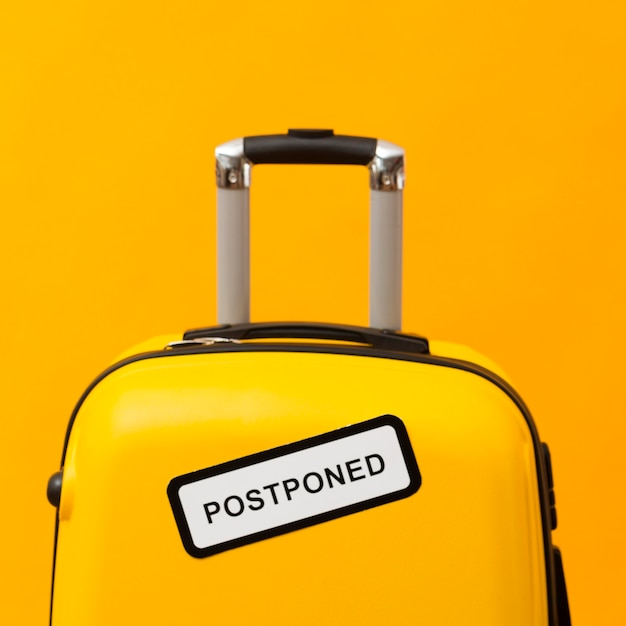 Yellow luggage with postponed sign Free Photo