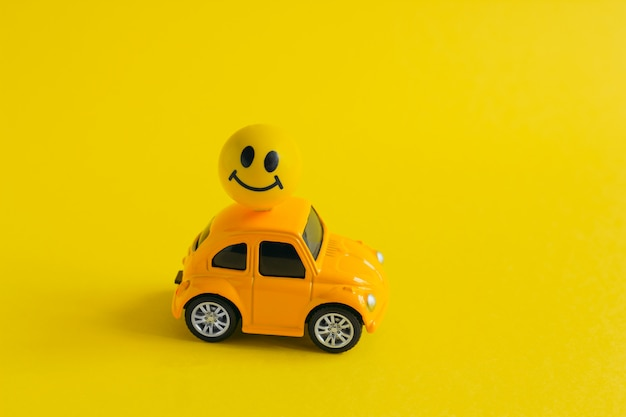 Yellow machine with ball with painted smiling face attached to the roof on yellow Premium Photo