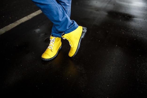 濡れた雨の通り背景に黄色の男の靴 無料写真