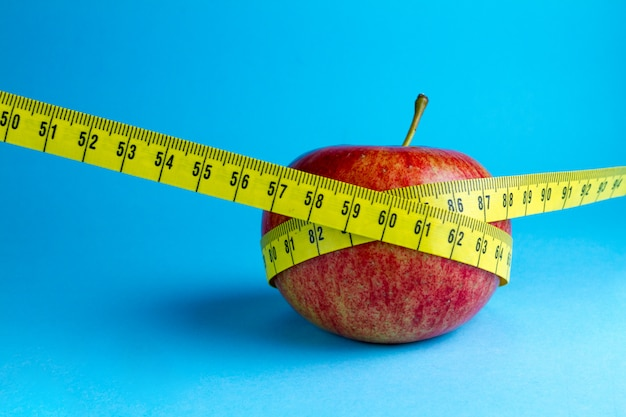 Yellow measuring tape and an apple Premium Photo