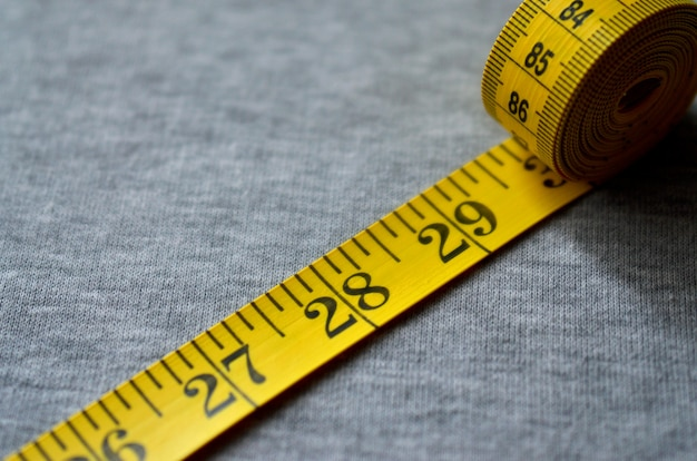 Yellow measuring tape lies on a gray knitted fabric Premium Photo