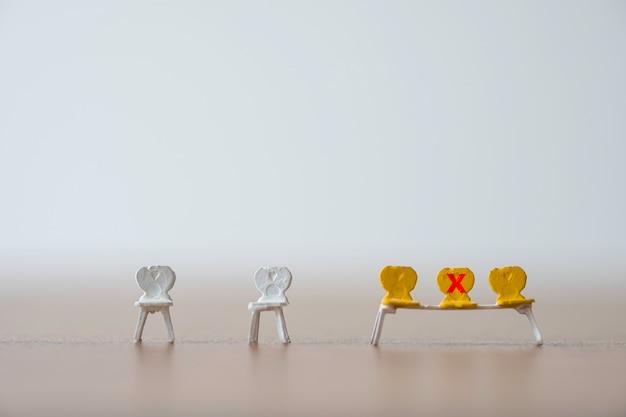 Желтый миниатюрный стул, отмеченный знаком красного креста, запрещает садиться, чтобы держать людей на расстоянии и предотвратить вспышку коронирусного вируса covid-19. концепция социального дистанцирования. Premium Фотографии