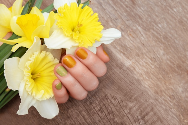 Yellow nail design. female hand with glitter manicure holding narcissus flowers. Free Photo