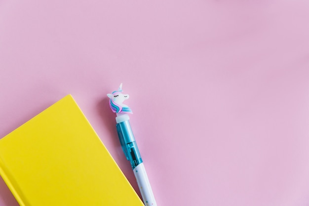 Yellow notebook for notes, funny unicorn pen on pink pastel background. flat lay. top view. copy space Premium Photo
