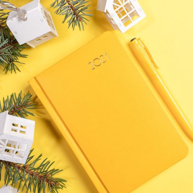 Желтый блокнот или ежедневник на 2021 год с еловыми ветками и декором. вид сверху. Premium Фотографии