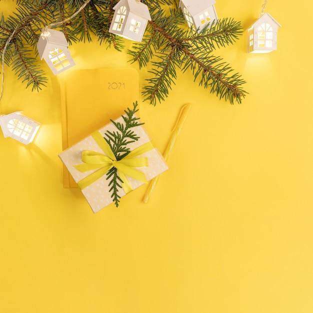 Желтый блокнот или ежедневник на 2021 год с еловыми ветками и подарочной коробкой. вид сверху. Premium Фотографии