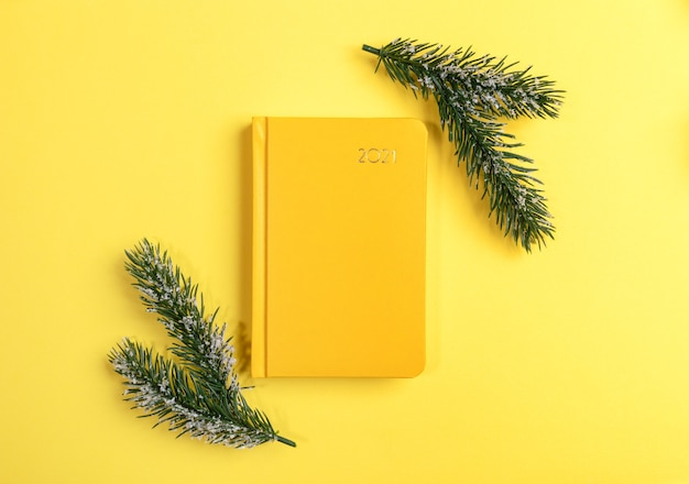 Желтый блокнот или ежедневник на 2021 год с еловыми ветками. вид сверху. Premium Фотографии