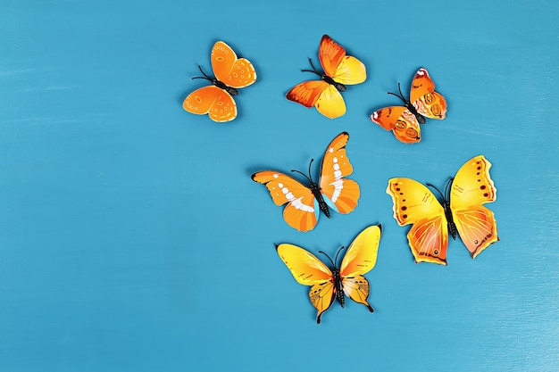 Yellow and orange butterflies on blue background. top view. summer background. flat lay. Premium Photo