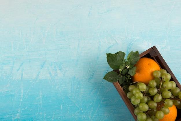 Arance gialle e un grappolo d'uva in una scatola di legno nell'angolo Foto Gratuite