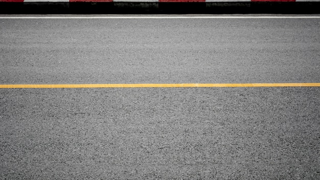 Yellow paint line on asphalt road - background Premium Photo