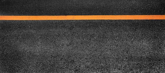 Yellow paint line on black asphalt. space transportation background Premium Photo
