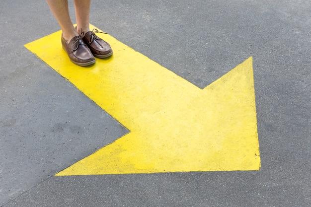 Freccia gialla dipinta nelle strade e nelle gambe Foto Gratuite