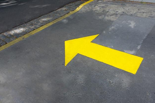 Freccia gialla dipinta nelle strade Foto Gratuite