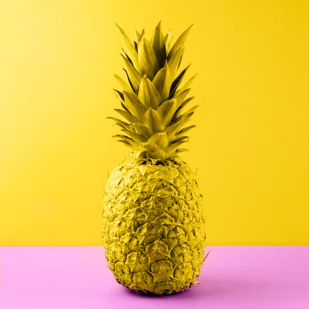 Yellow painted pineapple on pink desk against colored backdrop Free Photo