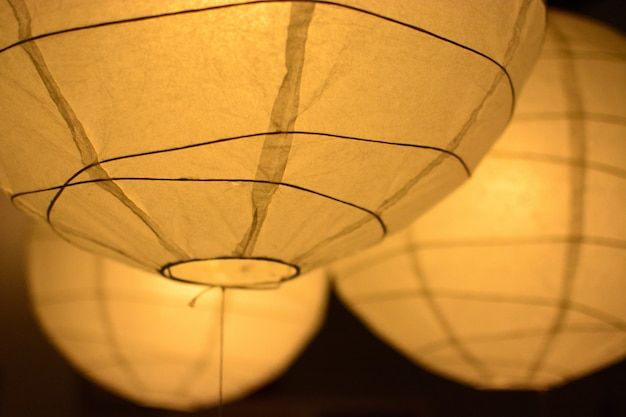Желтые бумажные фонарики на темном фоне Premium Фотографии