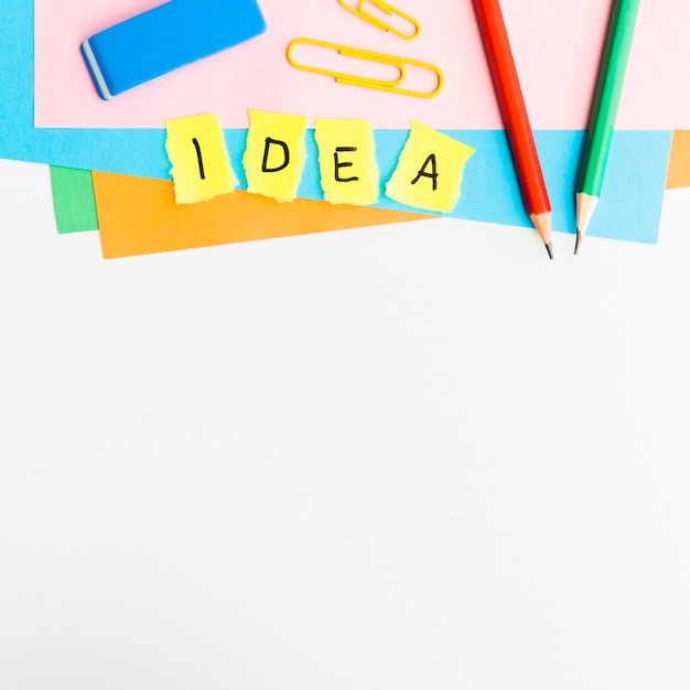 Yellow paper pieces with idea text with school supplies isolated on white background Free Photo