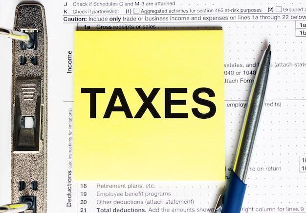 Желтая бумага с текстом налогов. финансовая концепция Premium Фотографии