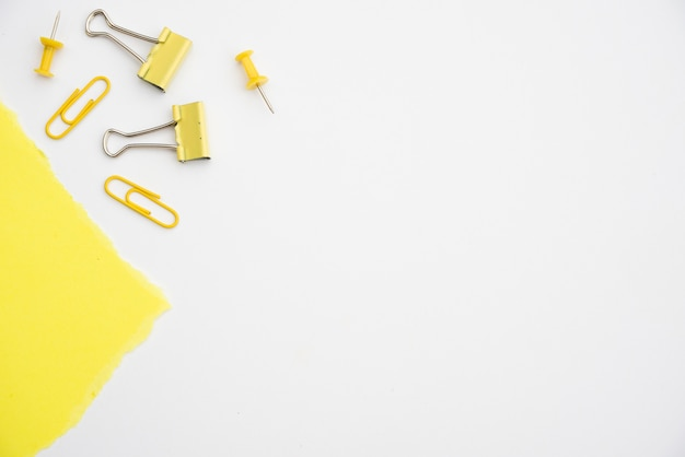Yellow paperclip and pushpin on white background with copy space Premium Photo